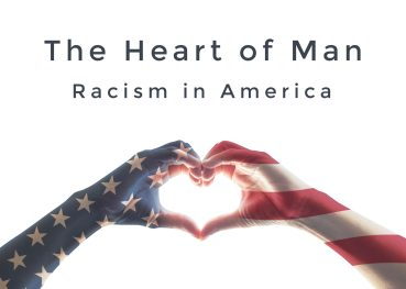Photo of a person making a heart with his or her hands. A transparent American flag shows through the hands and wrists. Pic represents The Heart of Man--Racism in America.