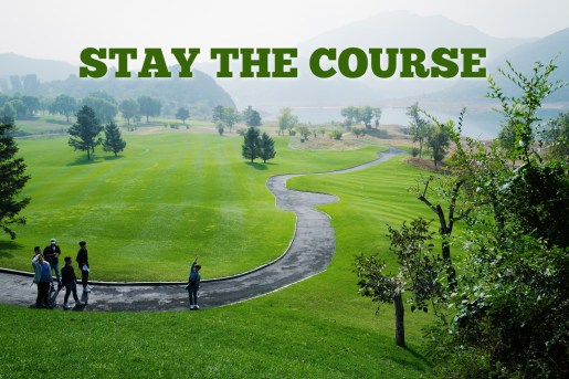 Photo of people standing on a paved road winding through a lush green meadow. Pic represents how one should follow God's directions and Stay the Course.