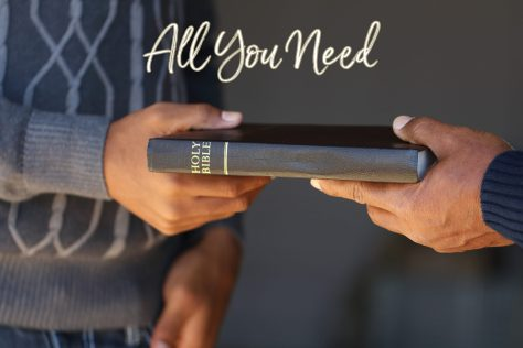 Photo of one person passing a holy Bible to another.  Pic represents All you Need is God's Grace.