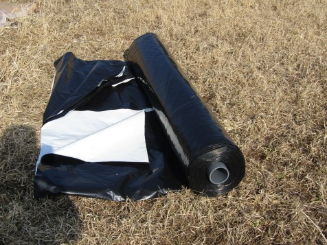 The silage tarp Scott ordered for me came in a long cardboard box and was wrapped and on a roll. After unrolling I could get a better feel for how it would open up. The tarp is rolled so you open it with the white side up, so we had to flip it over before fully opening it.