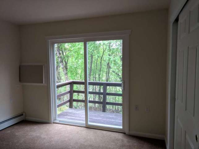 Bedroom looking out back deck and trees.
