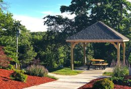 Springvale's small pavilion with a picnic table underneath. Red mulch landscaped path.