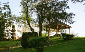 Pavilion on top of the hill with grass and bushes.