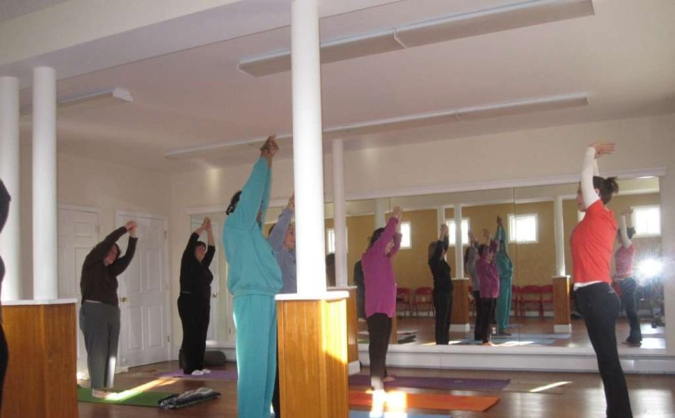 Yoga instructor and residents stretching arms over their heads.