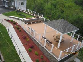 Deck with pavilion, white railings and landscaped walkway on the left.