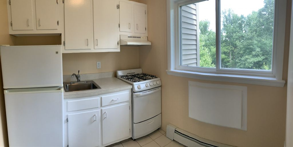 Kitchen with white cabinets and appliances. Large window looking outside at tree tops.