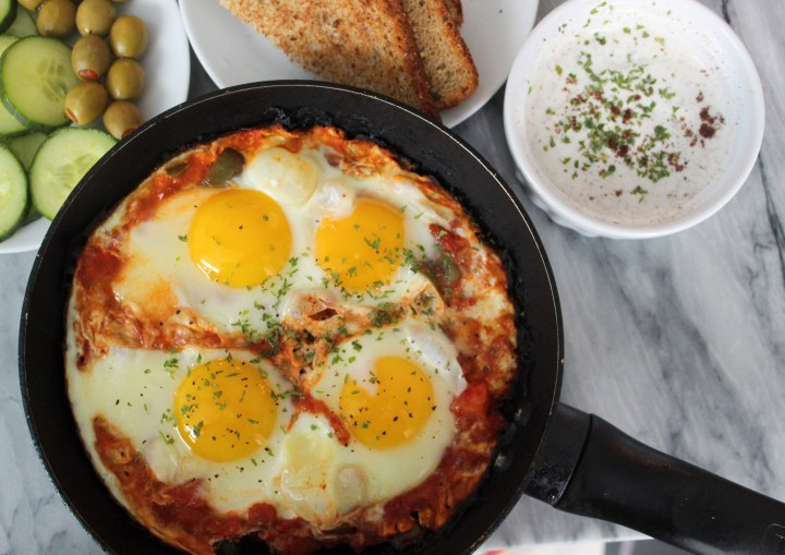 Turkish poached eggs - (menemen) served with olives and cucumbers