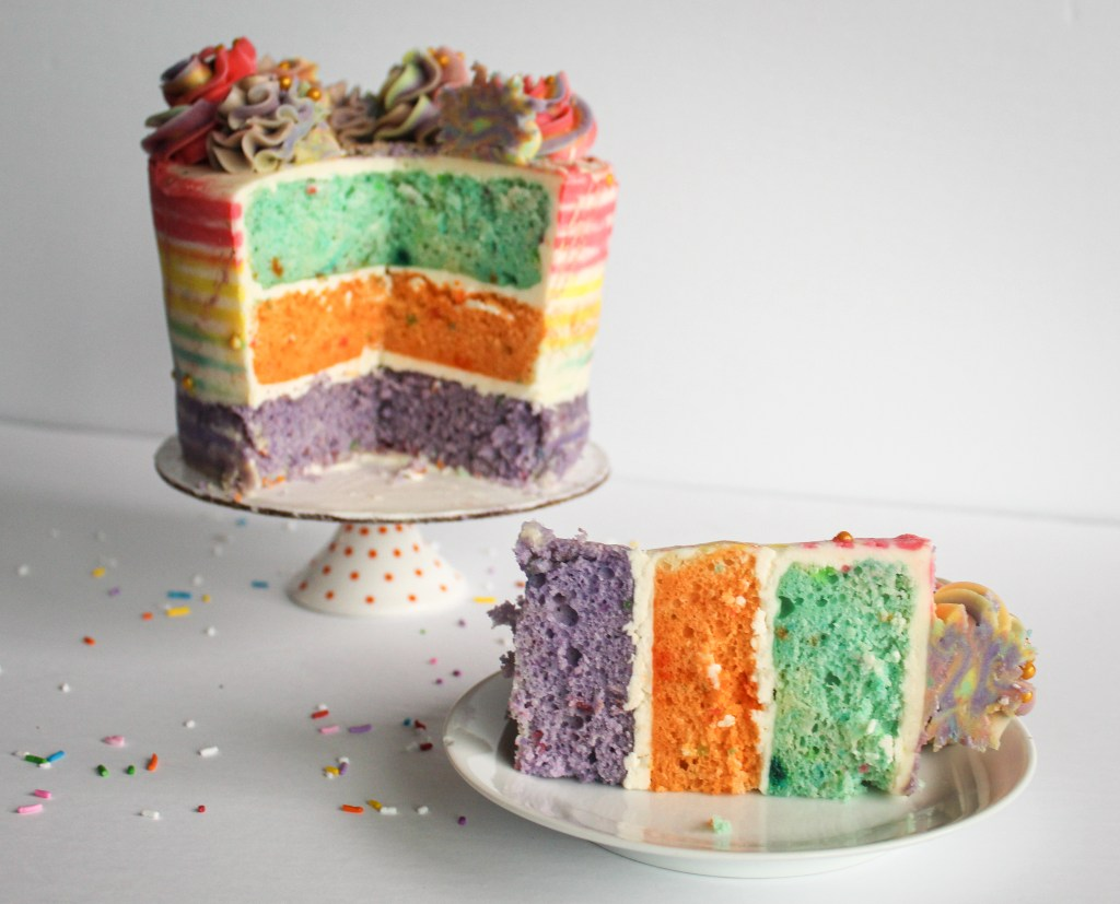 Rainbow striped cake inside with cake slice on white plate