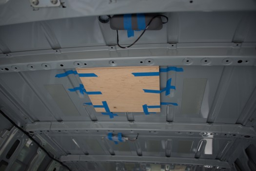 Wooden template in place ready to drill holes through to the outside of the roof. First holes through the van!