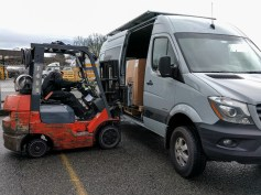 Seats being put into the van by a forklift truck