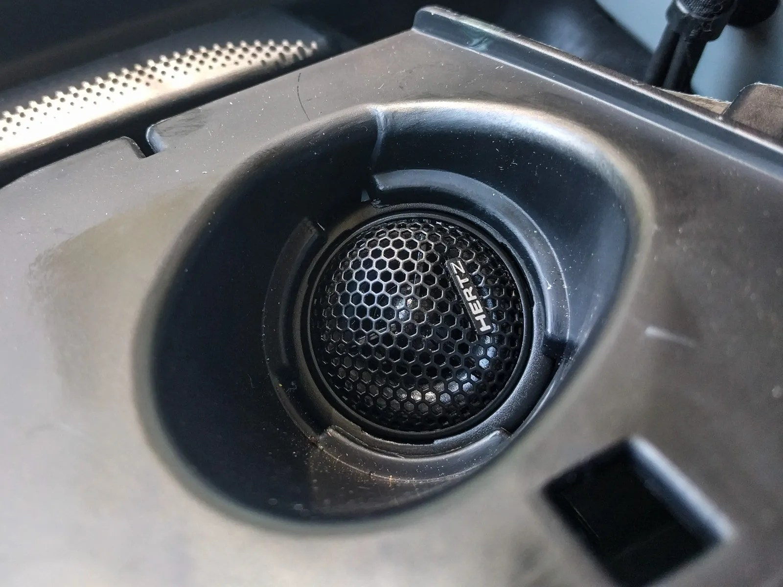 Pull the tweeter wire through to the underside of the tweeter surround, then crimp on butt connectors to join the tweeter wires to the ones coming from the crossover. Now you can push the tweeter into the underside of the surround. It should just clip in place.
