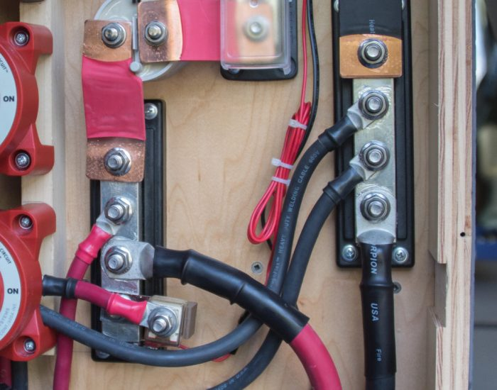 Positive and negative bus bars with 4/0 and 2 AWG cables attached