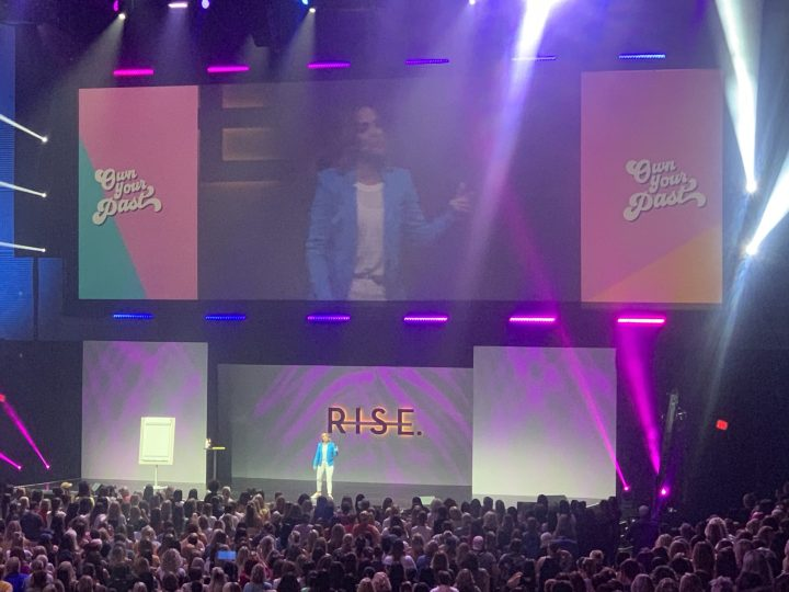 Colorful picture of Rachel Hollis opening up the Rise Conference in Dallas, Texas. She is speaking about owning your past. #sproutingvitality #ownyourpast #risexdallas #findyourtribe