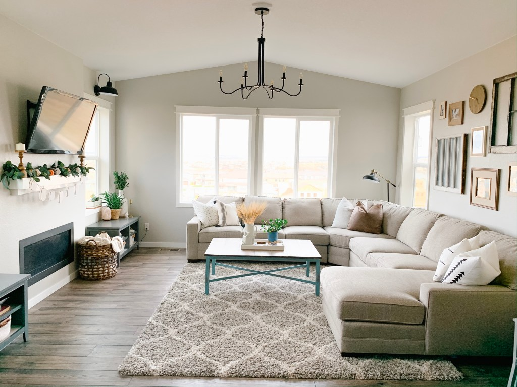 Living room with casing around windows and no blinds, it has a sectional couch and fireplace and painted gray.