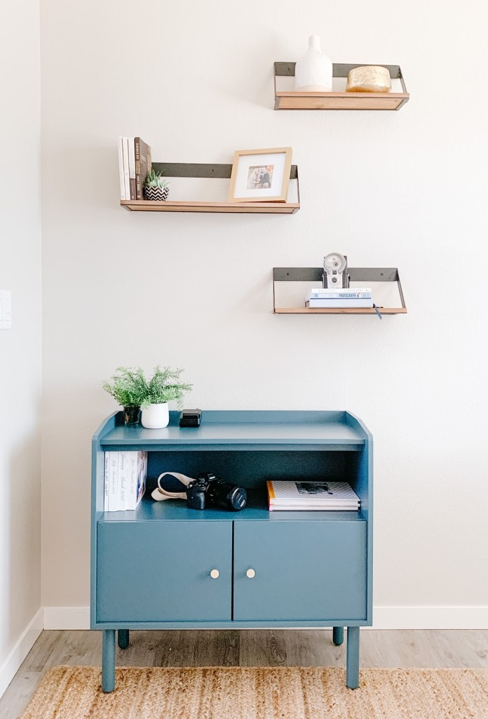 picture of a teal storage cabinet with 3 wall shelves above it in an office