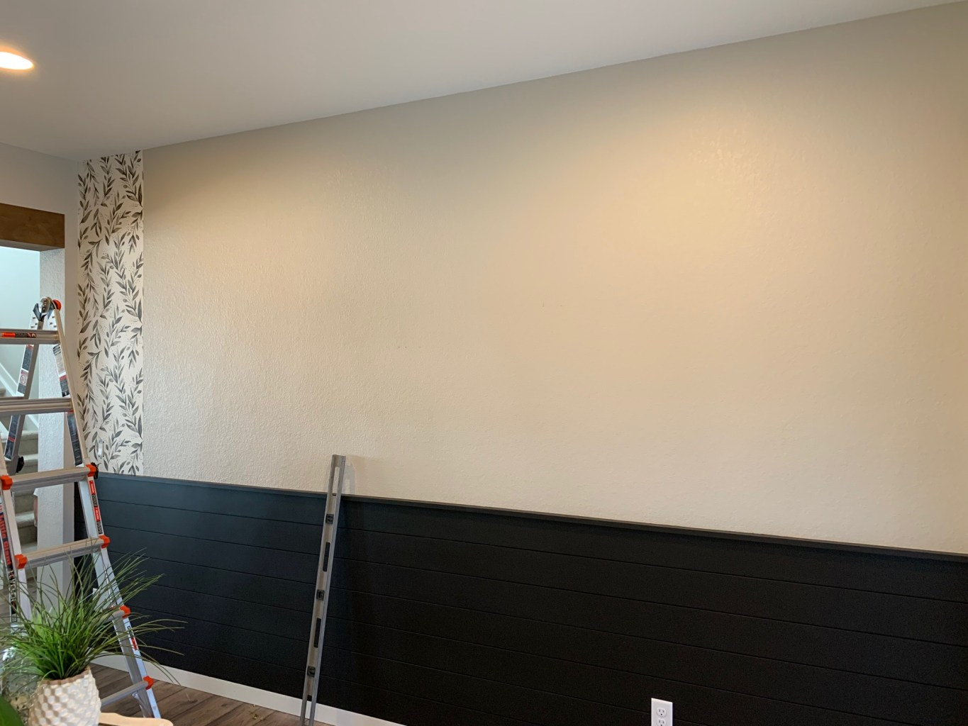 Entry wall with 1 strip of wallpaper and half the wall is black shiplap