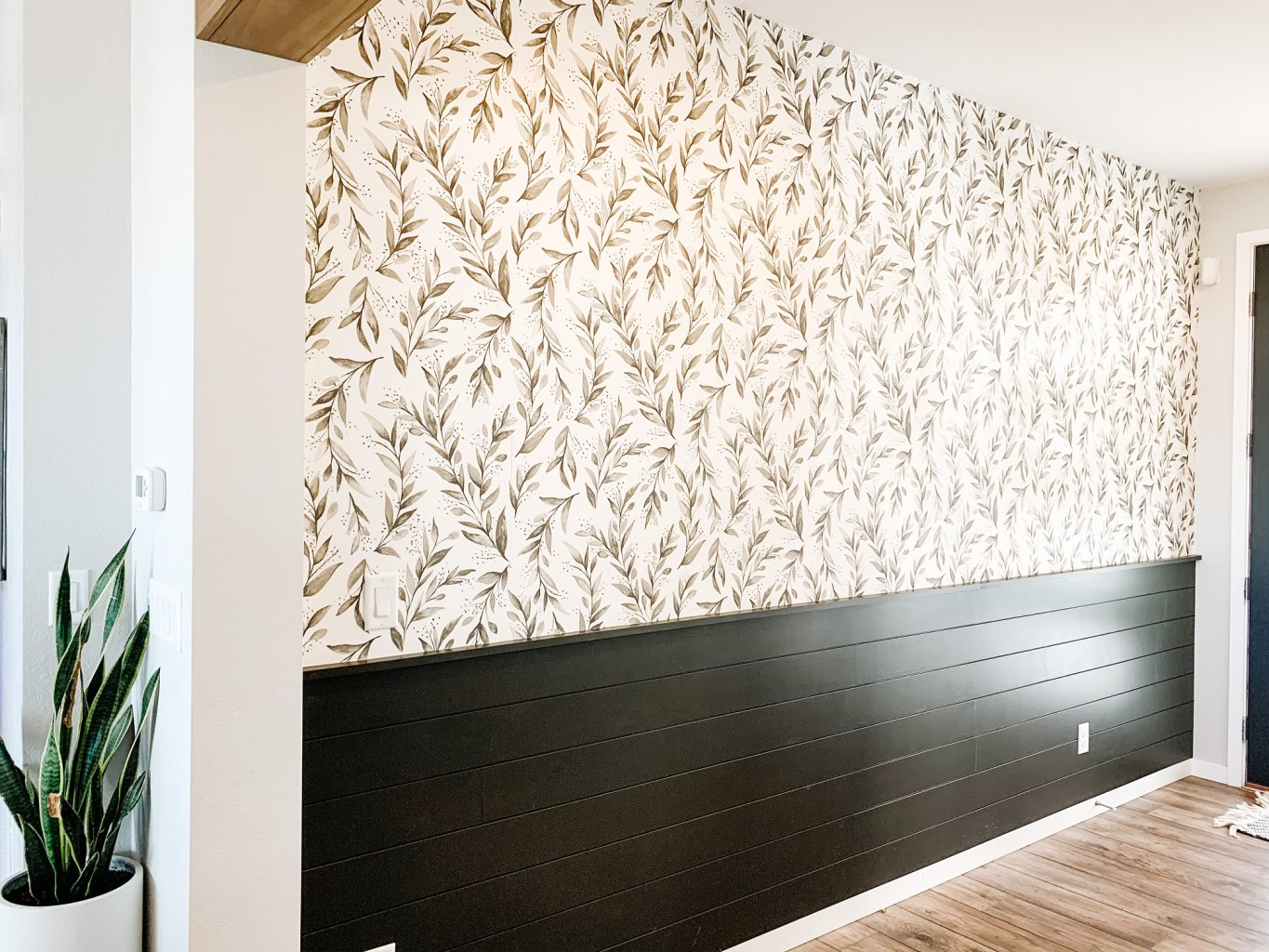 wall with half olive branch wallpaper and half black shiplap