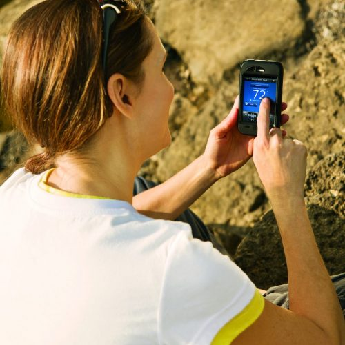 An image of a woman using the Comfort Sync app on her phone from the outdoors.