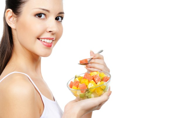 IBS-Diet-Swap-Woman-Eating-Fruit-Cup-Stomach-Problems-Spry.jpg