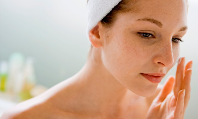 Woman putting on face lotion after facial