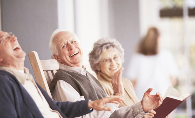 Elderly friends sit laughing on porch.