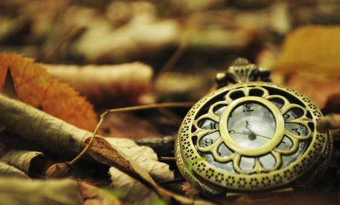 Clock in autumn leaves