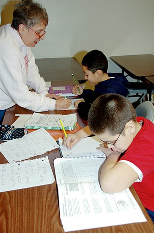 A volunteer helps students with their homework during the after school tutoring/homework club program.