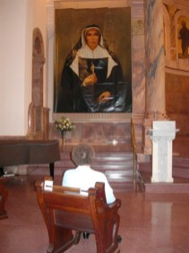 Sister Diane Ris, who was the general superior of the Sisters of Providence at the time of Mother Theodore's beatification, has a moment of reflection in front of the banner.