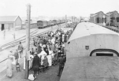 As train loads of wounded Chinese soldiers arrive in Kaifeng, Sisters of Providence and Benedictine Sisters aid in their care.