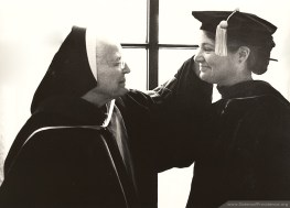 Sister Mary Joseph Pomeroy, former dean of students at Saint Mary-of-the-Woods college, assists Sister Rosemary Nudd in adjusting her new doctoral garb for a commencement ceremony in 1985.