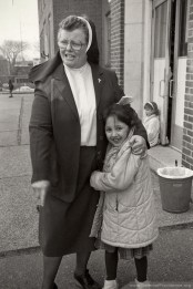 Sister Eleanor Hubner, principal of St. Rose School in Chelsea, Mass., exchanges hugs with a first grader at recess (1989).