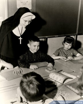 Sister Brendan Harvey (RIP) assists some students with their schoolwork. She began Cara School in Terre Haute, Ind. in 1969 to serve the needs of children with disabilities.
