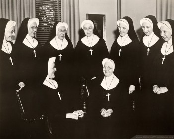 Principals of high school sponsored by the Sisters of Providence gather in 1963 for a meeting at Saint Mary-of-the-Woods. (Seated left) Sister Mary Joan Kirchner, Director of Education, converses with Superior General Mother Rose Angela Horan. (Standing left to right) Sisters Joseph Eleanor Ryan, Mary Xavier Coppersmith, Mary Raymond Schelhopf?, Dorothy Mary Noe, Mary Ellen Kilday, Miriam Joseph Cahill and Catherine Ursula Hayes.