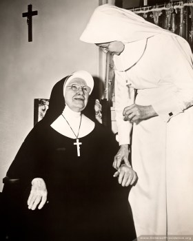 [Between 1954-1960] Sister Innocentia Ashley takes the pulse of Sister Agnes Cecile O'Connor. Sisters of Providence and lay staff members in Mother Theodore and Lourdes Halls continue the legacy of caring for our sisters who are ill.