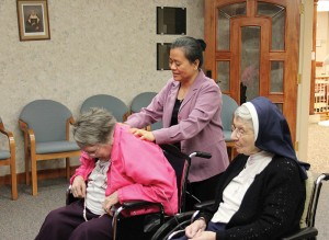 Sister Su-Hsin Huang, standing, gives a back massage to Sister Rita Lerner as she and Sister Rosalie Marie Weller, right, prepare to say their daily rosary in the Chapel at Providence Health Care.