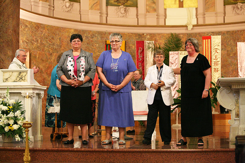 Four women professed perpetual vows as Sisters of Providence of Saint Mary-of-the-Woods on June 30. From left, Sisters Deborah Campbell, Laura Parker, Patty Wallace and Beth Wright stand before the gathered assembly in the Church of the Immaculate Conception at Saint Mary-of-the-Woods immediately after professing their vows.