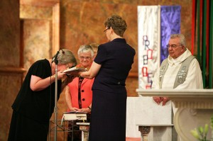 Sister Beth Wright kisses the Bible after professing her lifelong commitment as a Sister of Providence of Saint Mary-of-the-Woods during a liturgy on June 30. General Officer Sister Dawn Tomaszewski holds the Bible as General Superior Sister Denise Wilkinson and Father Daniel Hopcus look on.