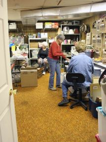 From left, volunteers Sharon Chrisman, Virginia Toppas and Erma Simson work in the housewares preparation and storage area in the back of the thrift store.