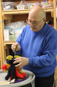 Volunteer Jerry Hixson, the toy tester, checks out a mechanical rooster to make sure it works.