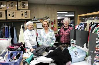 Faithful volunteers at The Helping Hands, from left, Milly Barbour, Bonnie Monaghan and Carol Robinson, have fun together while sorting and hanging clothes.