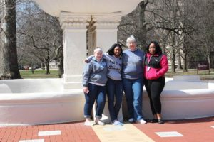 Sister Maureen Fallon poses with three of her former students at Providence Cristo Rey High School who went on to attend college at her alma mater, Saint Mary-of-the-Woods College.