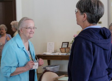 Sister Suzanne Dailey takes care of checking participants in at Monday's meeting. Here she greets Sister Judy Birgen.