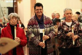 Jean Smith, Sarah Wilson and Traci Tucker carry candles during the entrance procession for their commitment ceremony as Providence Associates.