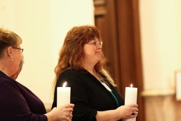 Jane Fisher and Donna Snelling carry remembrance candles during the entrance procession for the Providence Associates first commitment on Nov. 8, 2014, in the Church of the Immaculate Conception at Saint Mary-of-the-Woods.