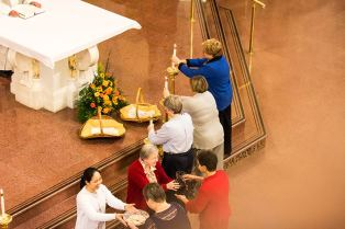 From left, Sister Maria Bui, OP, and Sister Emily Walsh receive the offeratory gifts from Marsha Bialaszewski and Marilyn Rausch as Helen Flavin, Jennifer Calvert and Marcy Meldahl place candles on the altar.