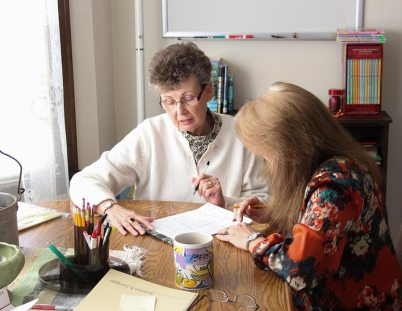 Sister Mary Tomlinson, development director for Guerin Outreach Ministries, offers support to Penny Sullivan, right, the program's director, in 2013.