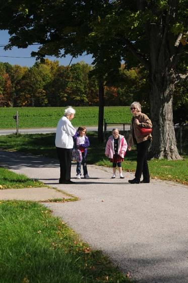 Sister Charles Van Hoy and another volunteer tutor meet their tutoring students at the bus stop in front of the Educational/Family Services building in 2012.