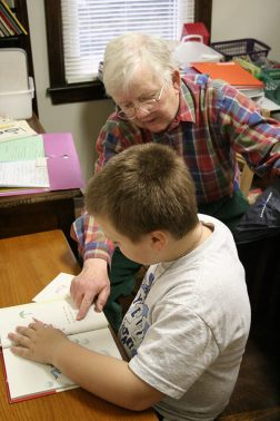 Sister Elizabeth Meyer helps a boy with his reading at EFS in 2008.