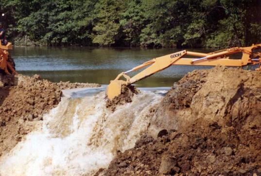 The final shovel-fulls of dirt are removed allowing the water to move into the newly expanded area of the lake in 1981.