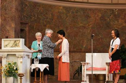 Sister Anna Fan (middle) receiving her cross from Sister Denise Wilkinson.
